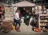 Brooklyn Flea Market customers gather around a booth selling vintage housewares